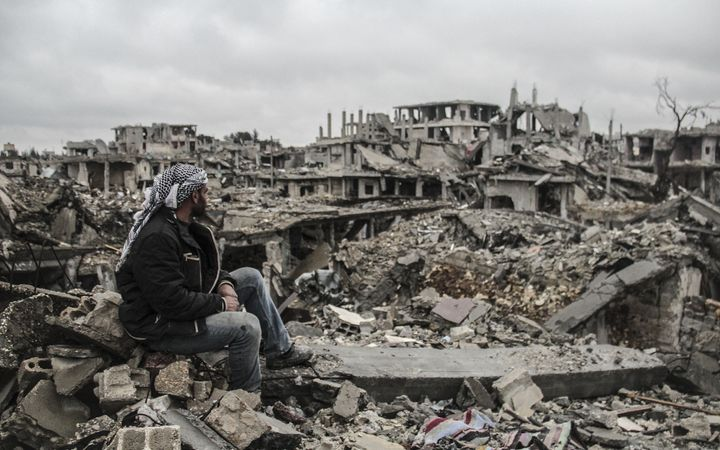 A man looks at the rubble of buildings destroyed in the clashes between Islamic State militants and Kurdish armed groups in t