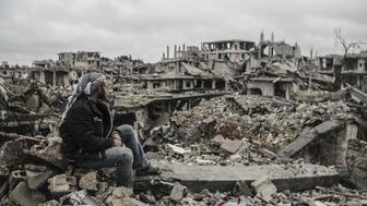A man looks at the rubble of buildings destroyed in the clashes between DAESH militants and Kurdish armed armed groups in the center of the Syrian town of Kobani (Ayn al-Arab), Aleppo on March 12, 2015 after it has been freed from DAESH militants. (Photo by Halil Fidan/Anadolu Agency/Getty Images)