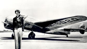 UNITED STATES - JANUARY 13:  Earhart (born 1897) standing in front of the Lockheed Electra in which she disappeared in 1937. Earhart began flying in 1920, and broke the women's altitude record in 1922. In 1928 she was invited to be the first woman to fly across the Atlantic and became an international celebrity. In May 1932 she became the first woman to fly solo across in the Atlantic. Earhart promoted aviation and helped found the Ninety-Nines, an organization dedicated to female aviators. On 1 June 1 1937, Earhart and navigator Fred Noonan left Miami, Florida on an around the world flight. They disappeared after a stop in Lae, New Guinea on June 29, 1937, with only 7,000 miles of the trip left. While a great deal of mystery surrounds her, her contributions to aviation and women's issues have inspired people for over 80 years.  (Photo by SSPL/Getty Images)