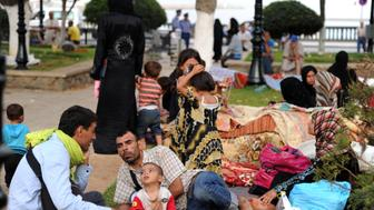 Syrian nationals fleeing the conflict in their home country gather in a garden in Port Said Square in Algiers on July 28, 2012. AFP PHOTO/FAROUK BATICHE           (Photo credit should read FAROUK BATICHE/AFP/GettyImages)