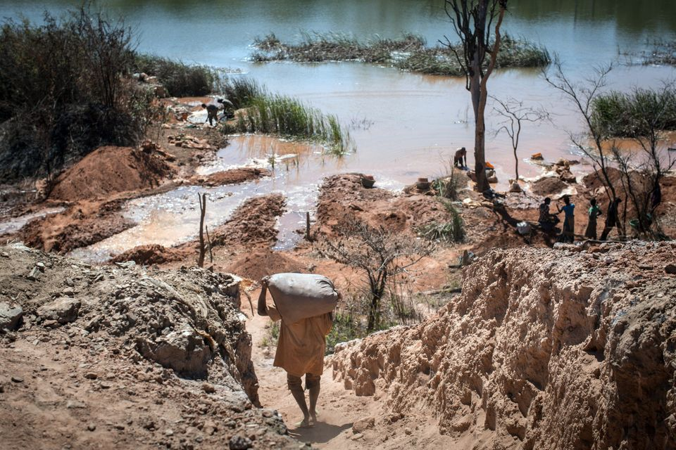 People separate cobalt from sand and rock in a lake in the Democratic Republic of the Congo last