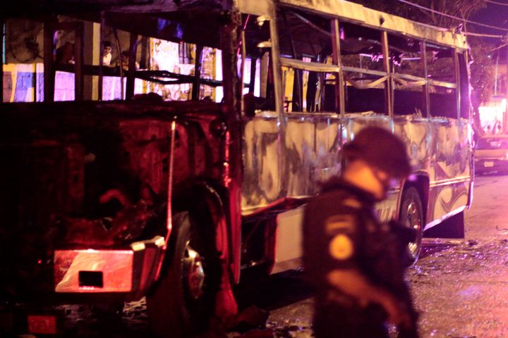 A police officer stands next to a burned bus in Acapulco, Mexico. The famous resort town is now the city with Mexico's highes