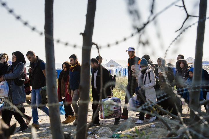 People walk across the border from Greece into Macedonia. The migrant and refugee crisis is causingEU member states to