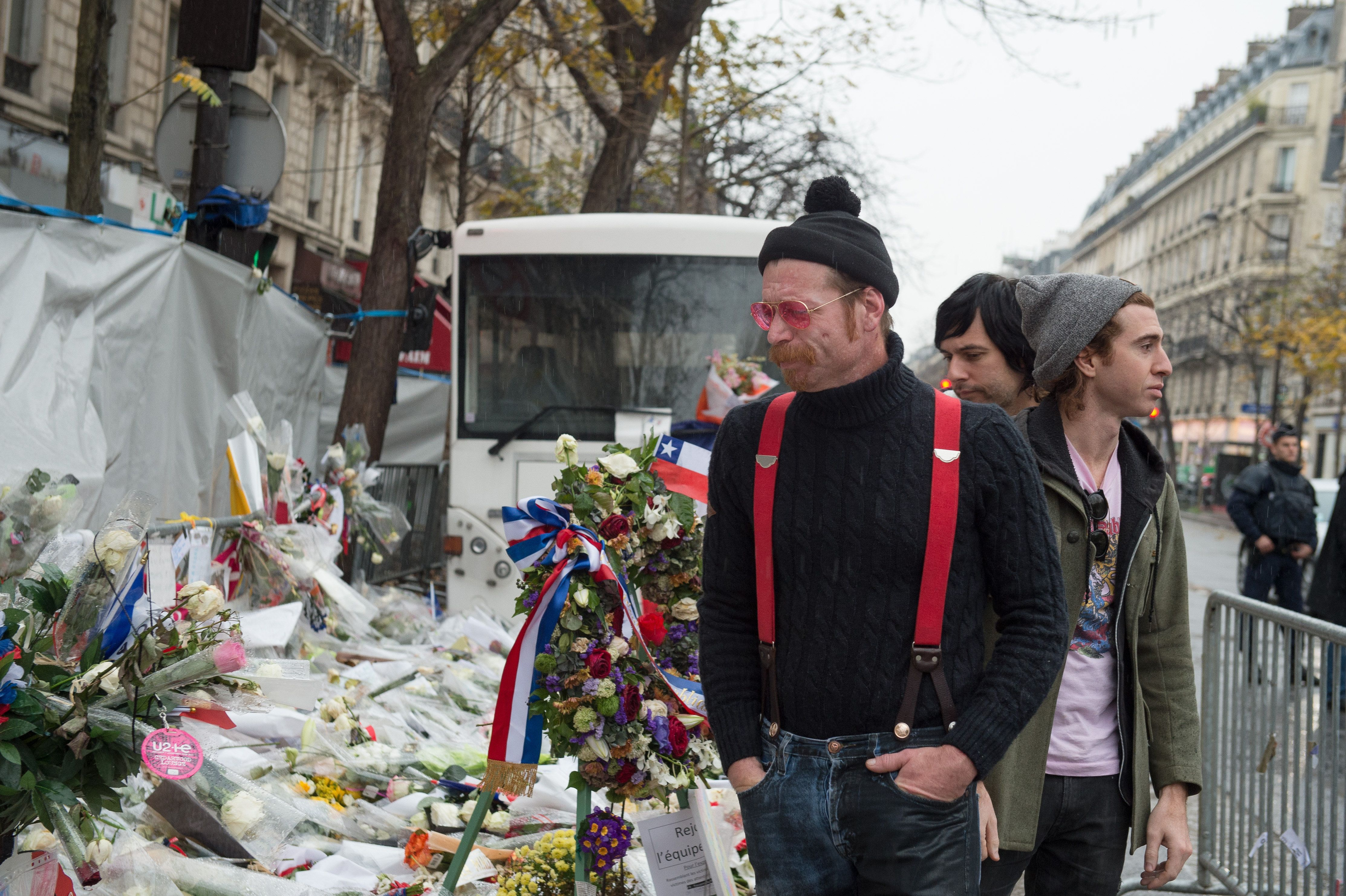 PARIS, FRANCE - DECEMBER 08:   Eagles of Death Metal frontman Jesse Hughes, guitarist Matt McJunkins and drummer Julian Dorio visit a memorial that pays homage to the victims of the terrorist attacks at Le Bataclan on December 8, 2015 in Paris, France.  The Eagles of Death Metal band returned to the Bataclan concert hall for the first time since the deadly terrorist attacks on November 13th where 130 people lost their lives and many more were injured. (Photo by David Wolff - Patrick/Getty Images)