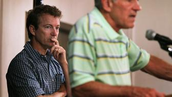 CEDAR RAPIDS, IA - AUGUST 10:  U.S. Senator Rand Paul (L) (R-KY) listens to his father Texas Congressman and Republican presidential hopeful Ron Paul speak at a campaign stop  August 10, 2011 in Cedar Rapids, Iowa. Most of the candidates hoping to receive the Republican presidential nomination are crisscrossing Iowa this week hoping to gain support in front of the Republican party debate and the Iowa Straw Poll.  (Photo by Scott Olson/Getty Images)