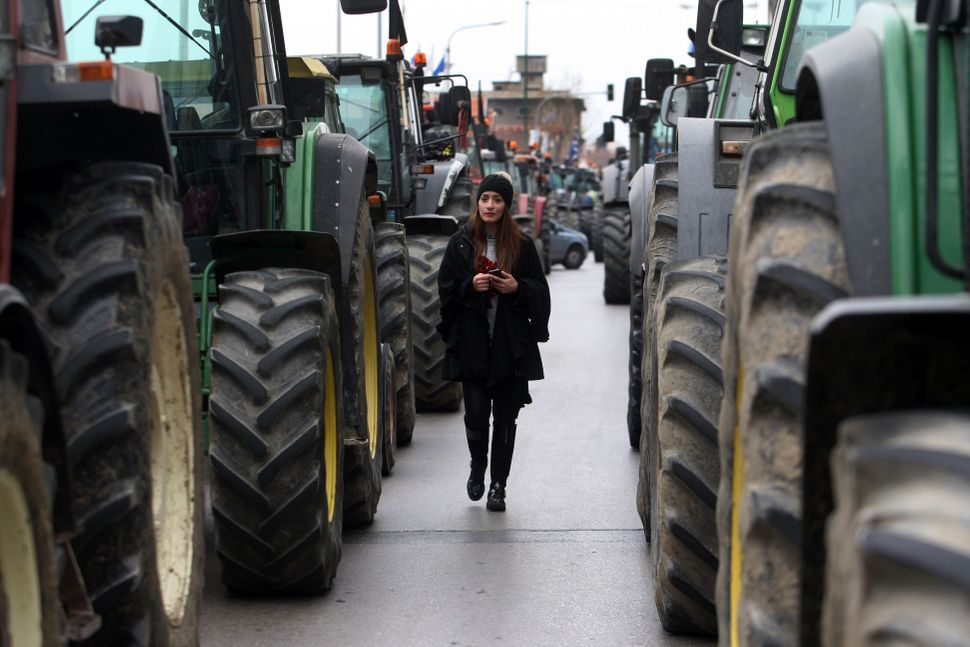 A woman walks in between tractors blocking a street in Thessaloniki on Jan. 20, 2016.