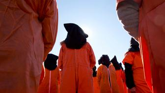 Protesters wearing orange jumpsuits depicting Guantanamo Bay detainees, participate in a rally outside of the White House in Washington Monday, Jan. 11, 2016, calling for a close of the detention center at the U.S. base at Guantanamo Bay, Cuba. (AP Photo/Carolyn Kaster)