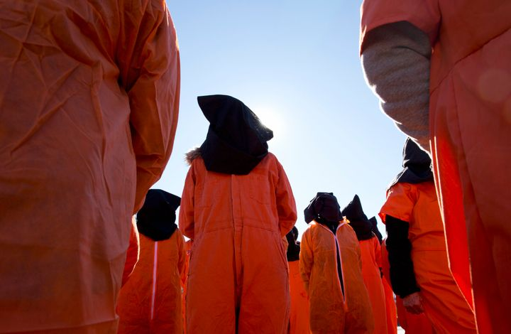 Protesters wearing orange jumpsuits depicting Guantanamo Bay detainees participate in a rally outside of the White House