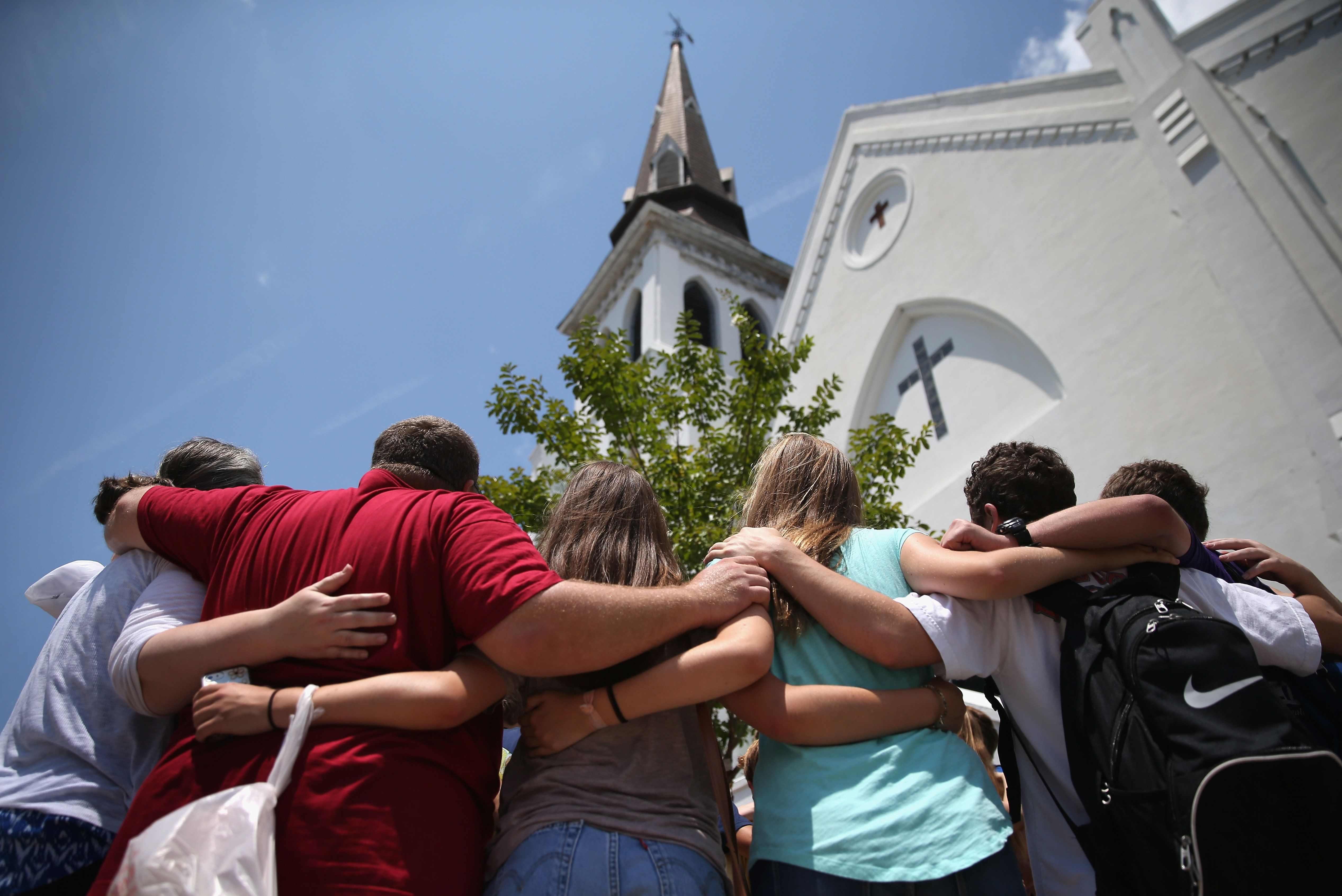 CHARLESTON, SC - JULY 17:  A church youth group from Dothan, Alabama prays in front of the Emanuel AME Church on the one-month anniversary of the mass shooting on July 17, 2015 in Charleston, South Carolina. Visitors from around the nation continue to visit a makeshift shrine in front of the church, in a show of faith and solidarity with 'Mother Emanuel', as the church is known in Charleston. Nine people were allegedly murdered on June 17 by 21-year-old white supremacist Dylann Roof, who was captured by police in North Carolina the following day. He is scheduled to go to trial July 11, 2016.(Photo by John Moore/Getty Images)