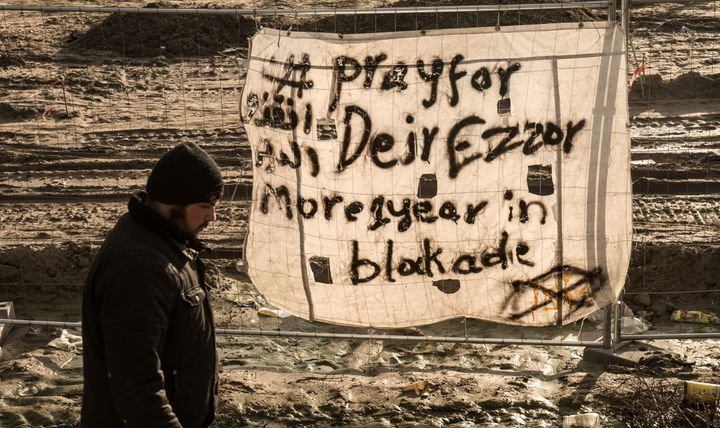 """Aman walks past a banner reading """"Pray for Deir Ezzor"""" at a campin December, 2015. Although Islamic State militan"""
