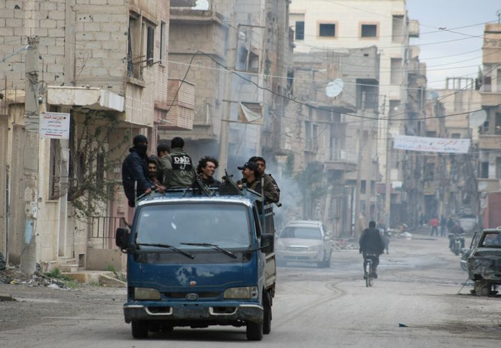 Syrian rebel groups drive through the eastern Syrian town of Deir Ezzor in 2014. Now, residents in thegovernment-contro