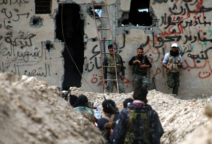 Fighters walk along a trench in Deir Ezzor. The Islamic State group blocks food from entering the town's neighborhoods,