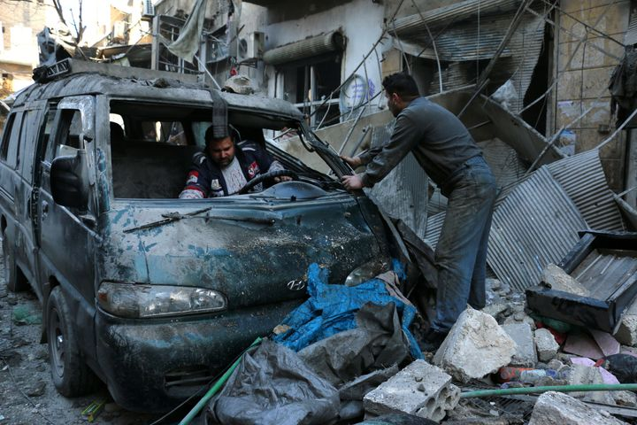 People inspect a damaged vehicle following a reported air strike by government forces on Aleppo, Syria. Deir Ezzor