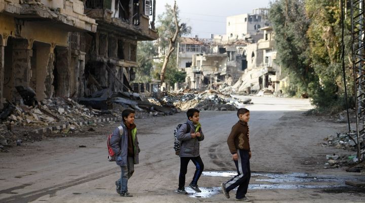 "Syrian children walk to school in Deir Ezzor in 2014. The ""double siege"" on government-controlled parts of the"