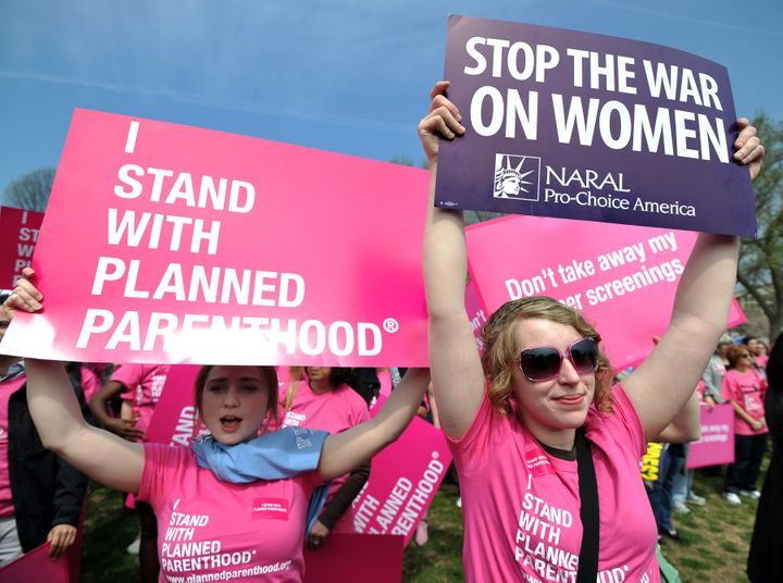 """Participants display signs at a rally to """"stand up for women's health"""" at the National Mall in Washington, DC, in April 2011."""