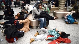 Passengers sleep on the ground as they wait for their flights at the Beijing Capital International airport, on November 23, 2015, after heavy snowstorm cancelled and delayed numerous flights in Beijing. AFP PHOTO / GOH CHAI HIN        (Photo credit should read GOH CHAI HIN/AFP/Getty Images)