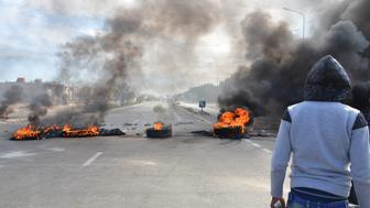 TATAOUINE, TUNISIA - JANUARY 21: Burning tires are seen at a blocked road during a protest, staged by unemployed young citizens against unemployment and poverty in Tataouine, Tunisia on January 21, 2016. Protests against unemployment and poverty spread along the country, has been started on 19th of January in Kassarine, Tunisia. (Photo by Mohamed Mdalla/Anadolu Agency/Getty Images)