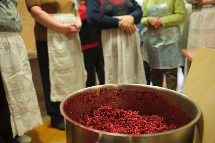 Women stand behind a pot filled with grain porridge during the preparation of Estonian blood sausages.