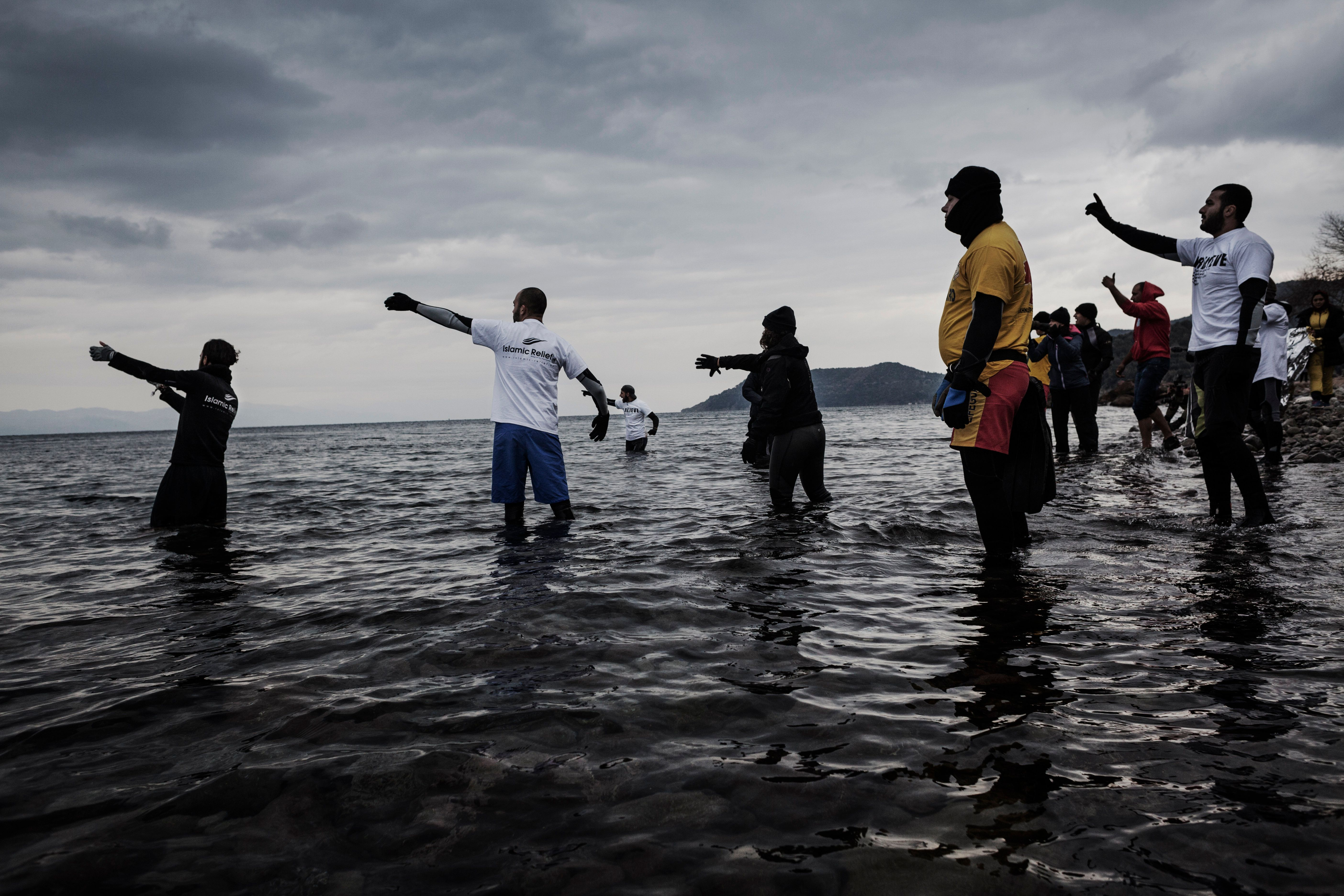 At least 42 people drowned after their boats capsized off Greek islands on Friday. Volunteers signal to an incoming rubber bo