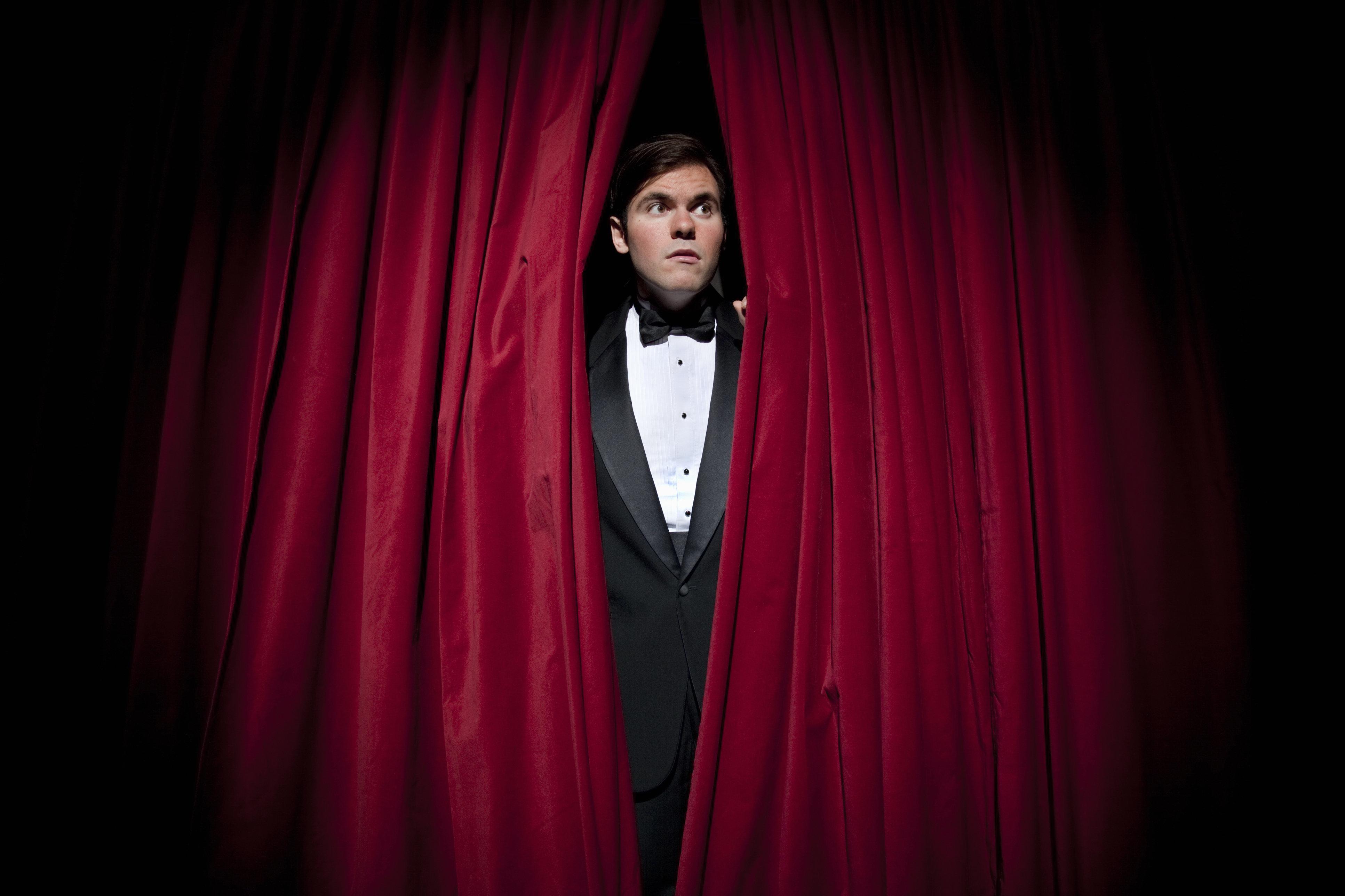 Man in tuxedo peeking through curtain