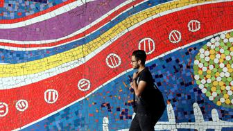 An Iranian man walks past a mural on a street in the northwest of the capital Tehran, on October 19, 2015. President Barack Obama ordered the US government to take steps towards lifting sanctions on Iran, in line with the nuclear deal struck between world powers and Tehran in July. AFP PHOTO / ATTA KENARE        (Photo credit should read ATTA KENARE/AFP/Getty Images)