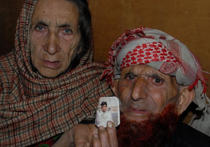 The parents of Shafqat Hussain, a Pakistani convicted of murder at age 14, hold a photograph of their son in Muzaffarabad, th