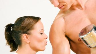 Couple in gym setting. He is lifting dumbbells, she is kissing his biceps. Sport does make sexy inde