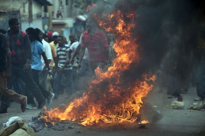 Demonstrators burn tires during a protest in Port-au-Prince, on January 22, 2016.