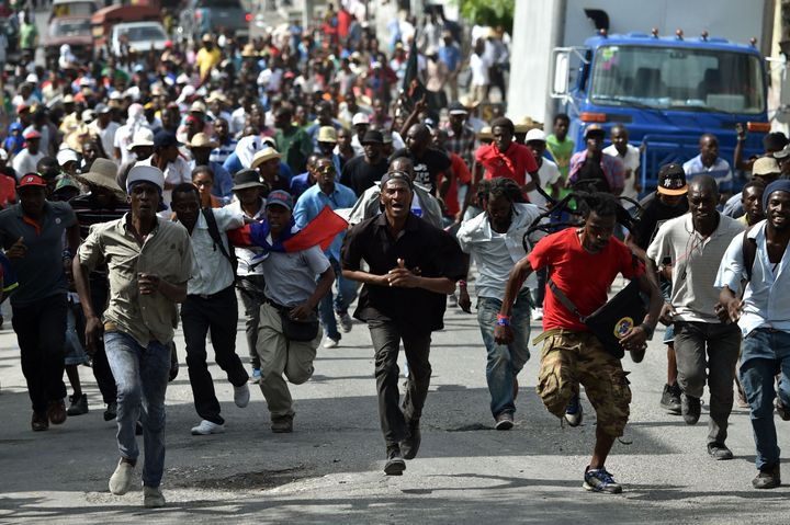 Demonstrators run during a protest in Port-au-Prince, on January 22, 2016.