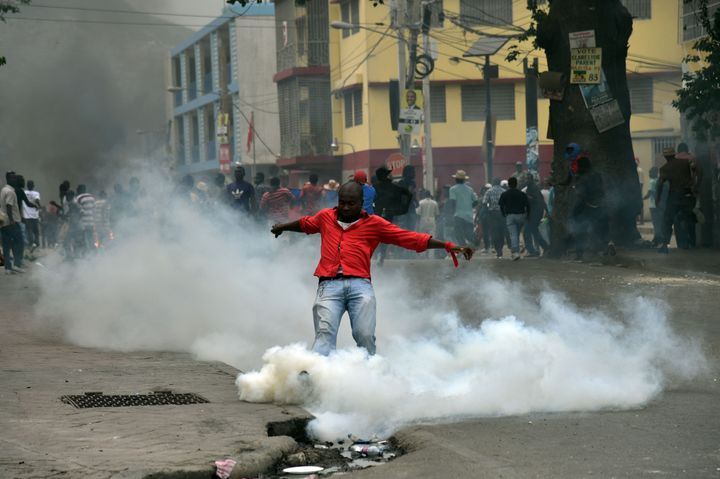 A man kicks a canister with a tear gas during a protest in Port-au-Prince on January 22, 2016.