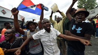 Demonstrators runing while perfom a voodoo ceremony prior a march, in Port-au-Prince, on January 22, 2016. Demonstrators marched to protest against the presidential elections. Haiti's electoral authority has postponed Sunday's planned presidential run-off amid mounting opposition street protests and voting fraud allegations. The second round of presidential elections was scheduled for January 24 between ruling party candidate Jovenel Moise and Jude Celestin but was suspended by CEP. / AFP / HECTOR RETAMAL        (Photo credit should read HECTOR RETAMAL/AFP/Getty Images)