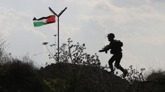 A member of the Israeli security forces runs past a Palestinian flag during clashes with Palestinian stone throwers in the West Bank town of Tulkarem on November 10, 2015. AFP PHOTO / JAAFAR ASHTIYEH        (Photo credit should read JAAFAR ASHTIYEH/AFP/Getty Images)