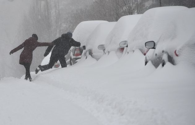 People cross a snow bank to get to the sidewalk on a residential street in Washington, DC on