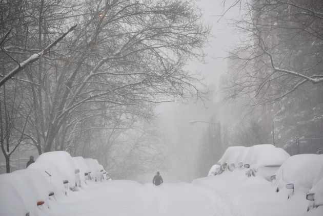 A pedestrian walks in the center of a snow-covered residential street in Washington, DC, on