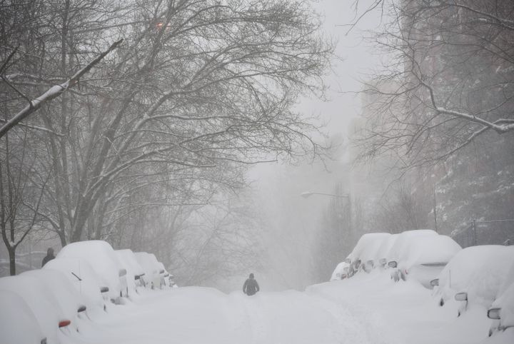 A pedestrian walks in the center of a snow-covered residential street in Washington, DC, on Saturday.