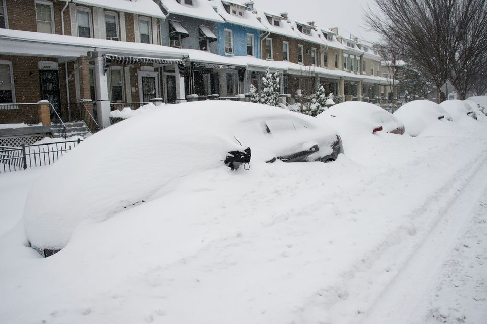 Parked cars are snowed in during a snowstorm in Washington, DC, on January 23, 2016. A deadly blizzard with bone-chilling win