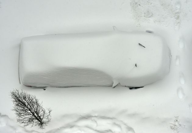 A snow covered car is seen from the roof of a building in Washington on Jan. 23,