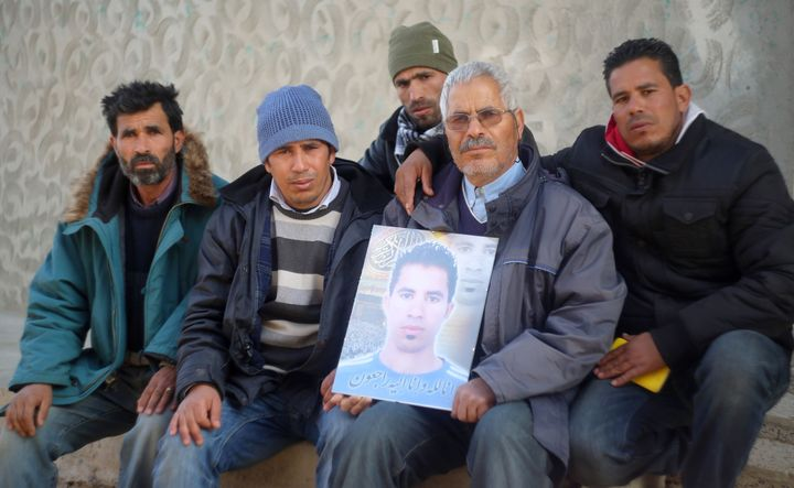 Othman Yahyaoui (C) poses with family members holding a portrait of his son, Ridha Yahyaoui, for a photo in Kasserine on