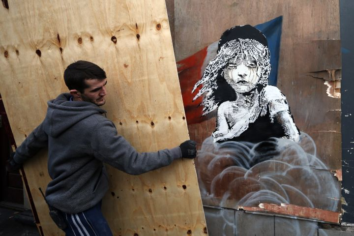 Builders cover a Banksy artwork shortly before being told to take it down from the building opposite the French embassy on Ja