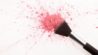 Makeup brush and pink blush powder splatter