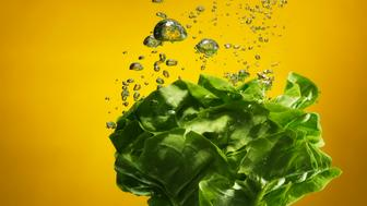 green salad splashed into water, creating bubbles, on yellow backdrop