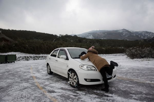 A woman builds a snowman on her car on top of Yangmungshan National Park on Jan. 25.
