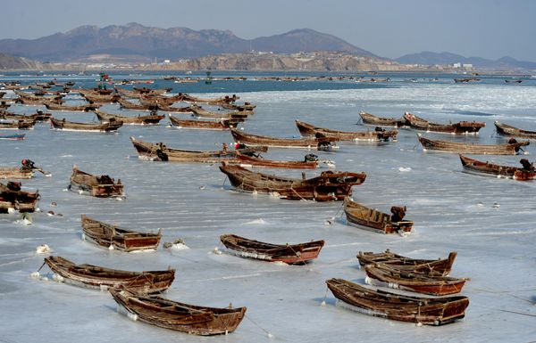 Fishing boats are stuck in ice at a harbor in Dalian on Jan. 21.