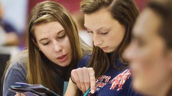 WINDHAM,  ME - NOVEMBER 6: Windham High School hosted an interactive career fair hosted by Jobs for Maine Graduates. Windham juniors Melanie Aldrich (left) and Joelle Bochus look over a brochure from the University of New Hampshire at the career fair. (Photo by John Ewing/Portland Press Herald via Getty Images)