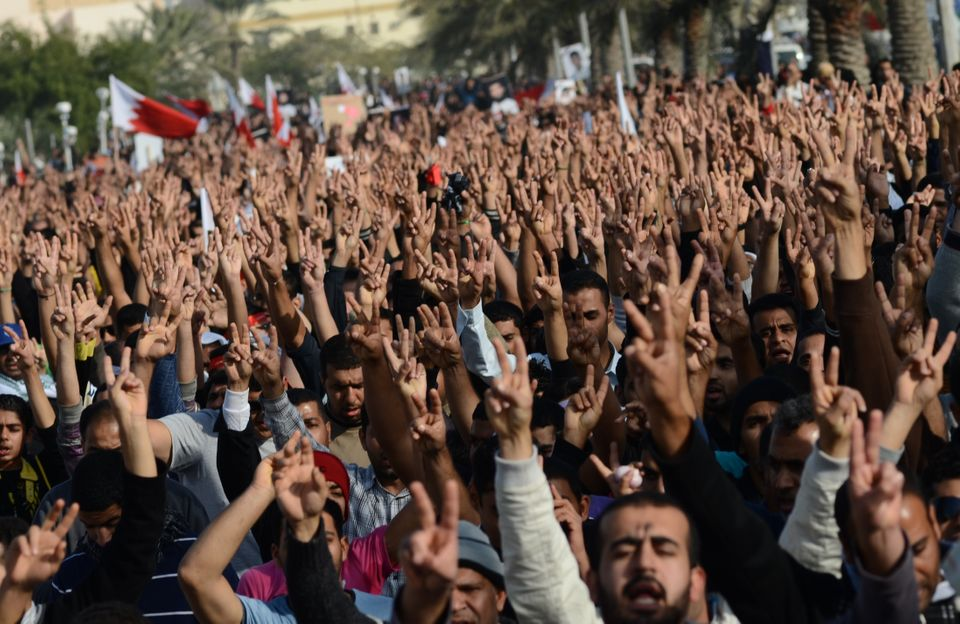 Bahraini Shiite Muslim mourners flash victory signs during Ali al-Qassab's funeral in Abu Saiba, Dec. 17, 2011.