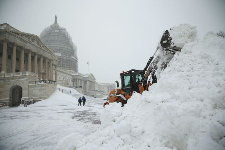 A bulldozer clears snow on the East Front of the U.S. Capitol on Jan. 23, 2016, in Washington.