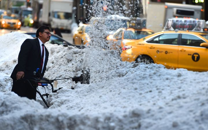 A worker clears snow on Third Avenue in New York City on Jan. 25, 2016, as New Yorkers return to work after a recor