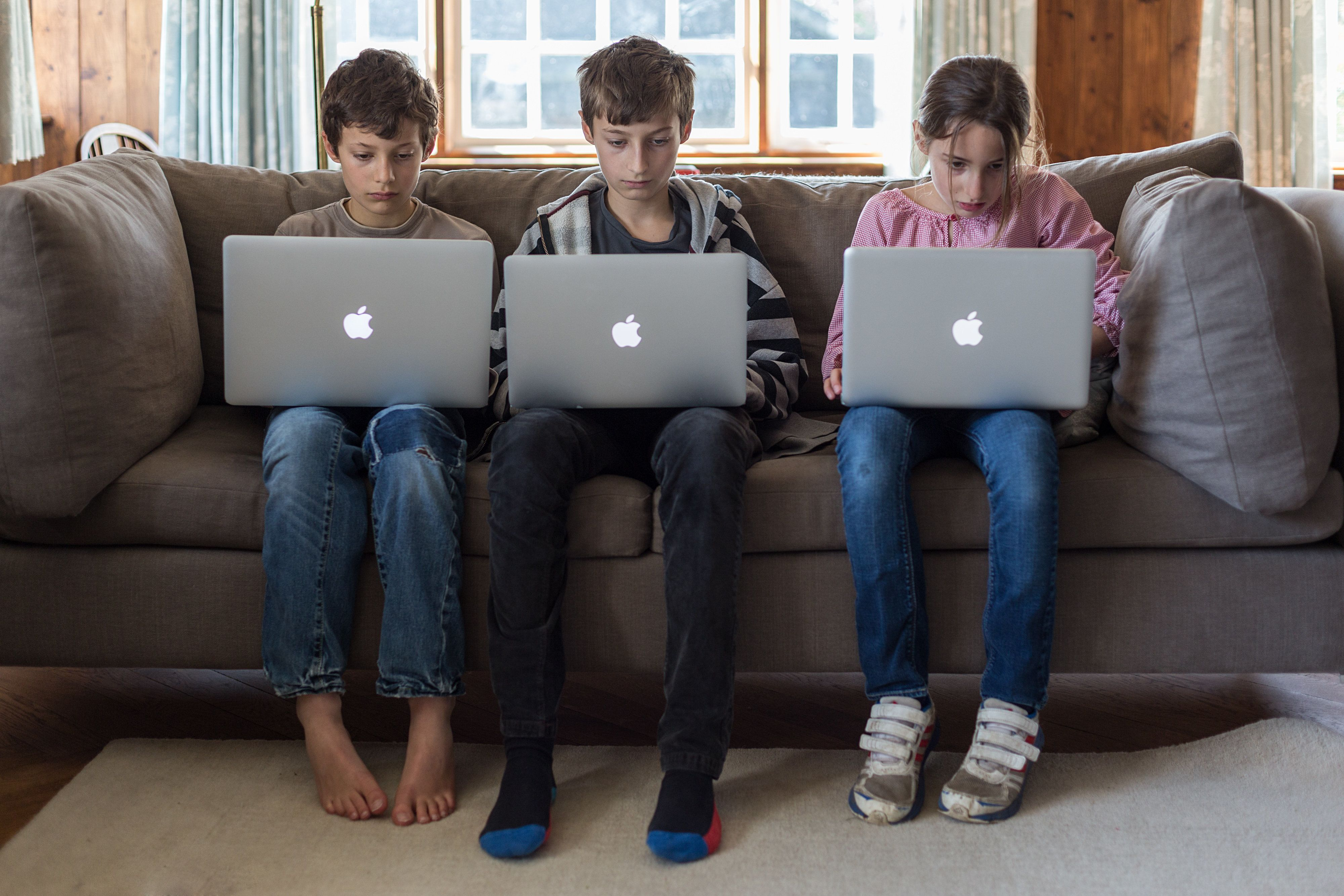 Three kids intensely playing on laptops