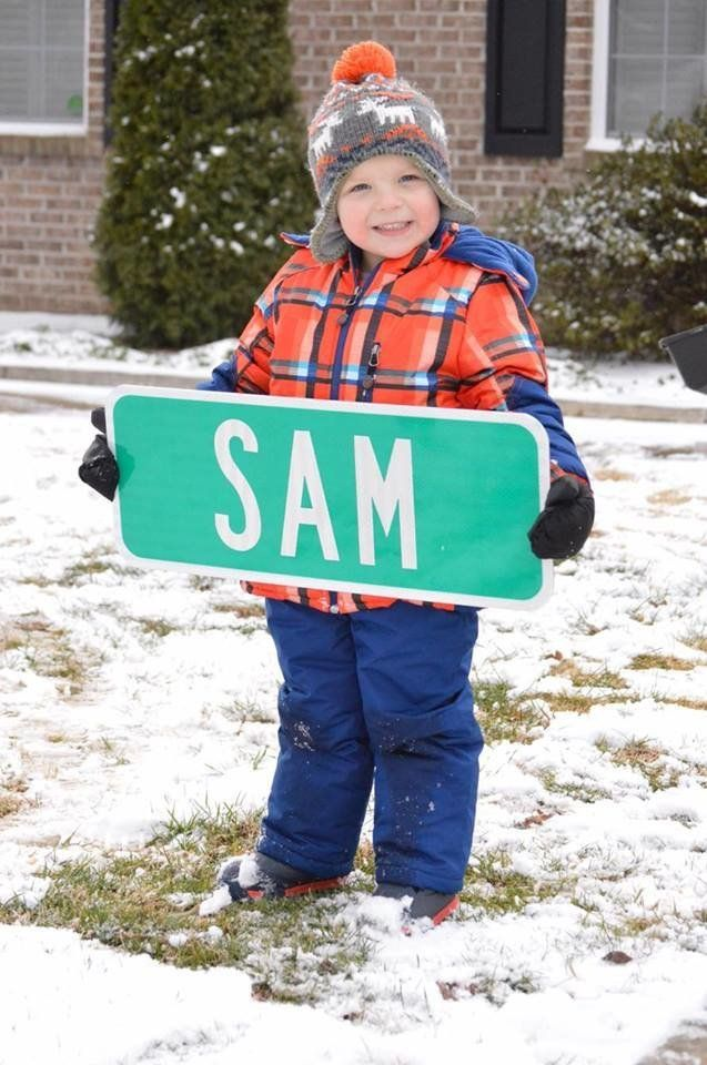 Sam holding a street sign with his name.