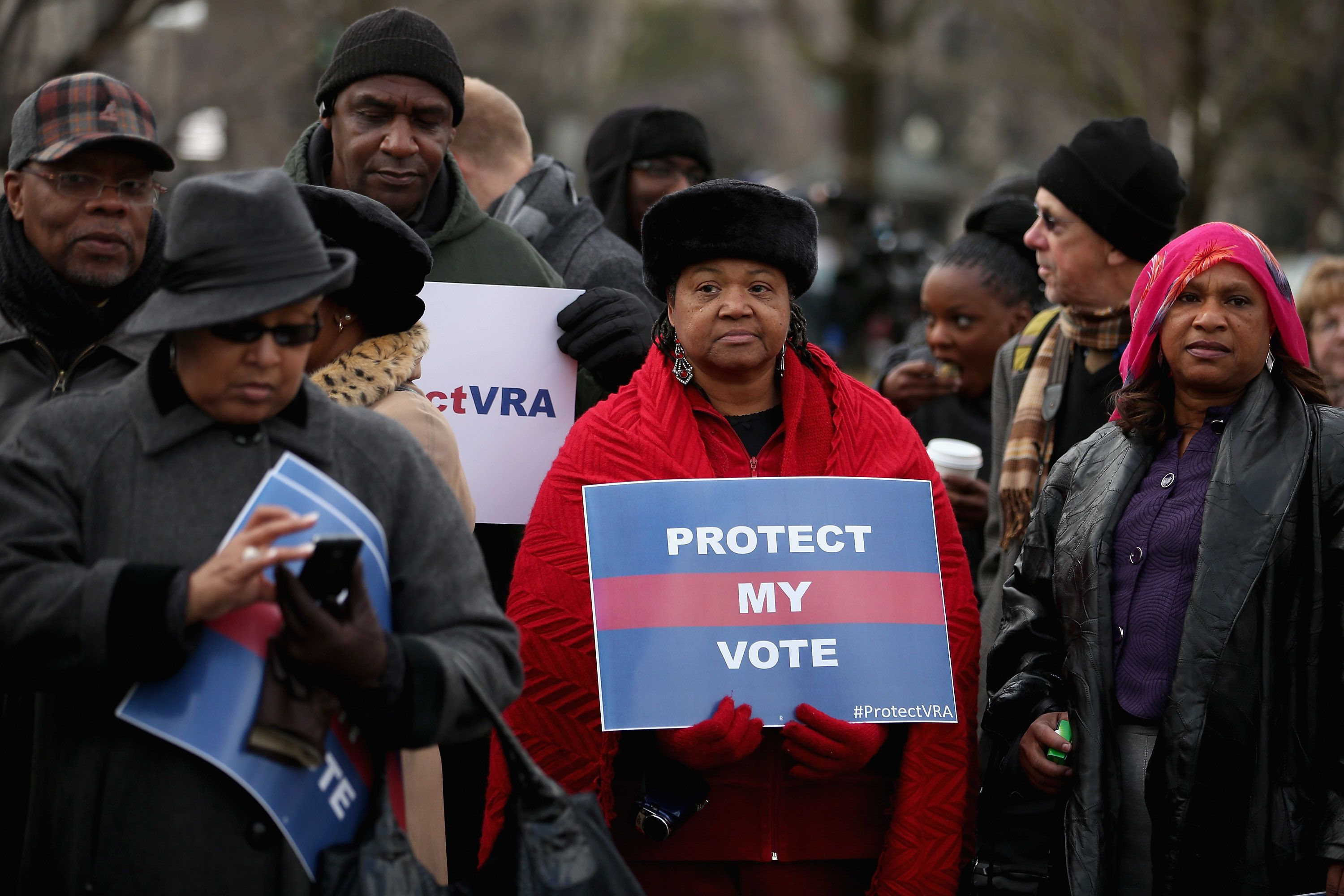 Demonstrators stand outside the U.S. Supreme Court in February 2013 as it hears arguments in the historic Shelby County v. Ho
